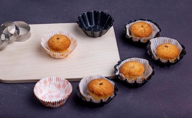 Vista lateral de muffins en moldes de papel sobre una tabla para cortar madera y cortadores de galletas en rústico