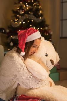 Vista lateral de la mujer abrazando a su osito de peluche en navidad