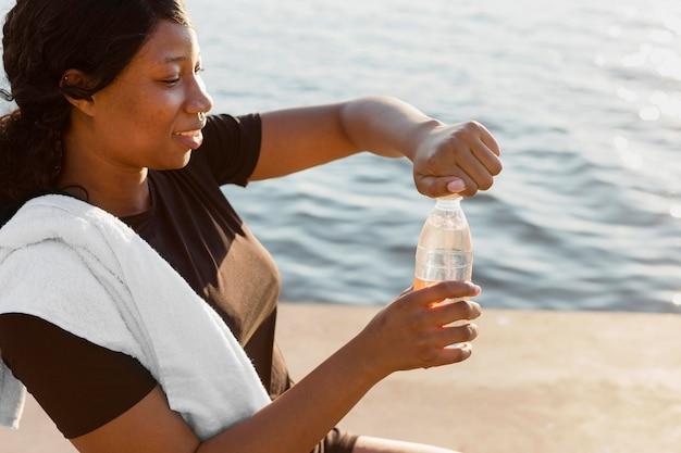 Vista lateral de la mujer abriendo la botella de agua después de hacer ejercicio