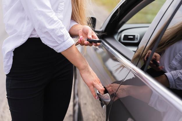 Vista lateral de la mujer abriendo la puerta del coche