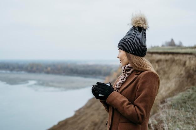 Vista lateral de la mujer admirando el lago con