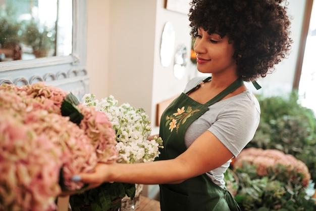 Vista lateral de una mujer afro-africana que mira el ramo de flores