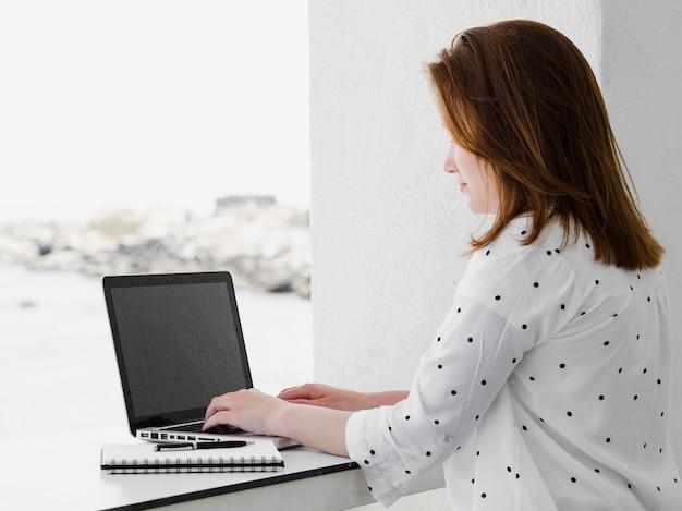 Vista lateral de la mujer afuera trabajando en la computadora portátil