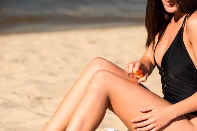 Vista lateral de la mujer aplicando protector solar en la playa con espacio de copia