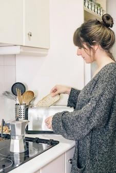 Vista lateral de una mujer asar pan en tostadora