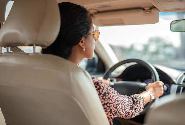 Vista lateral, de, mujer asiática, conducir coche