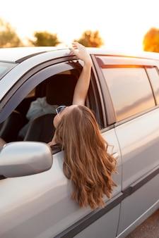 Vista lateral de la mujer asomando la cabeza del coche al aire libre