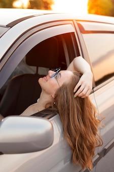 Vista lateral de la mujer asomando la cabeza fuera del coche