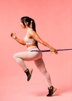 Vista lateral de la mujer atlética con banda de resistencia