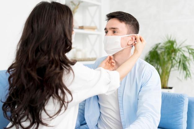 Vista lateral de la mujer ayudando al hombre a ponerse la mascarilla