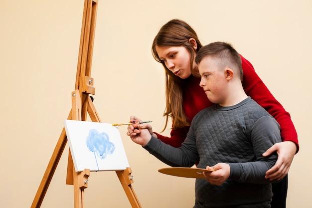 Vista lateral de la mujer ayudando a niño con pintura de síndrome de down
