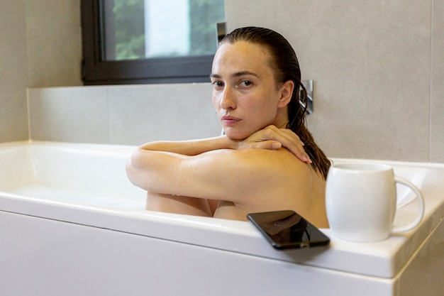 Vista lateral mujer en la bañera mirando a la cámara