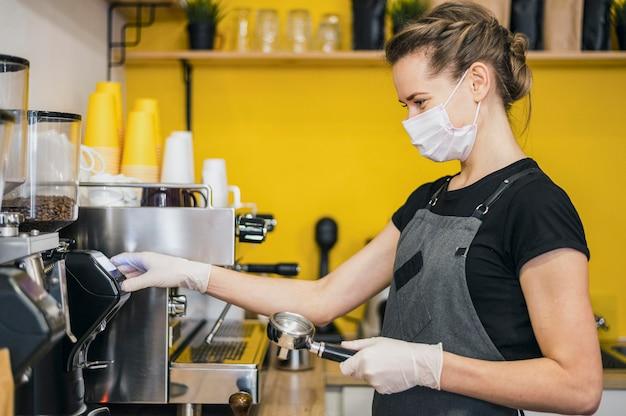 Vista lateral de la mujer barista con guantes de látex preparando café para máquina