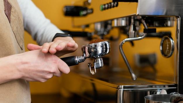 Vista lateral de la mujer barista con máquina de café