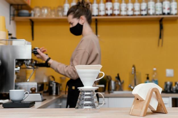 Vista lateral de la mujer barista con máscara trabajando en la cafetería.