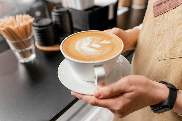 Vista lateral de la mujer barista sosteniendo una taza de café decorada en las manos