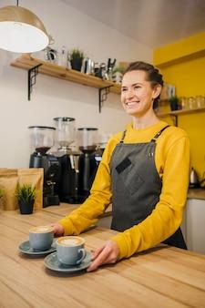 Vista lateral de la mujer barista con tazas de café.