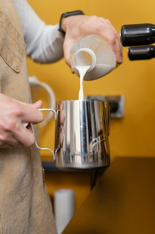 Vista lateral de la mujer barista vertiendo leche en taza