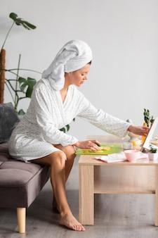 Vista lateral de la mujer en bata de baño complaciéndose en el cuidado personal