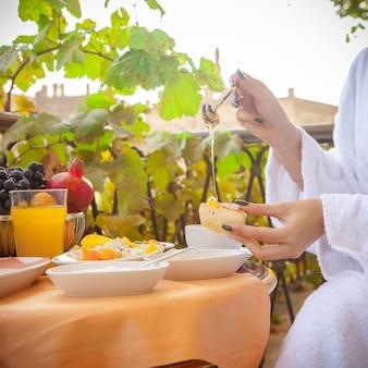 Vista lateral mujer en una bata de baño desayunando afuera en la mañana.