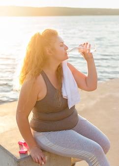 Vista lateral de la mujer bebiendo agua por el lago después de hacer ejercicio