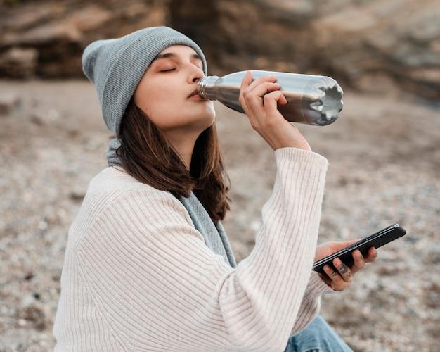 Vista lateral de la mujer bebiendo mientras usa el teléfono inteligente en la playa