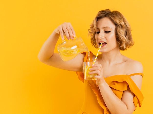 Vista lateral mujer bebiendo y vertiendo limonada