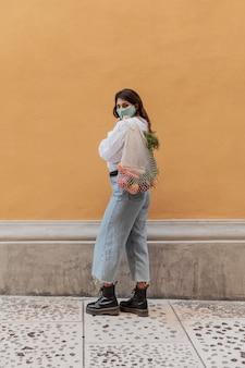 Vista lateral de la mujer con bolsas de la compra al aire libre