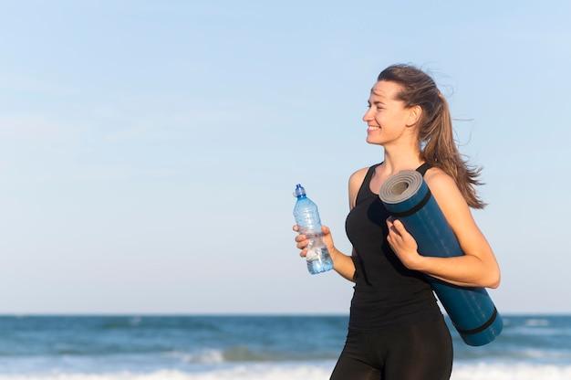 Vista lateral de la mujer con botella de agua y esterilla de yoga en la playa