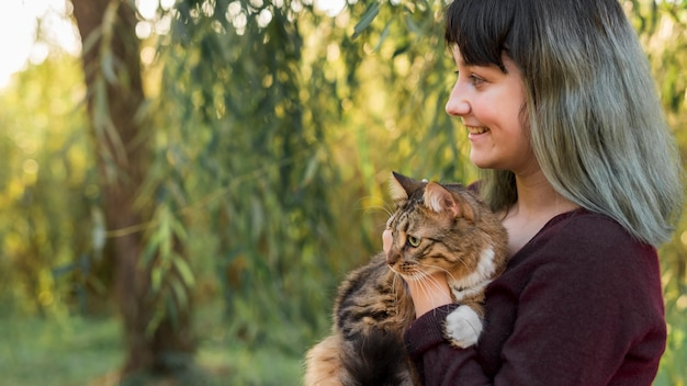 Vista lateral de una mujer de cabello teñido abrazando a su gato atigrado en el bosque