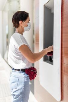 Vista lateral mujer en cajero automático con máscara