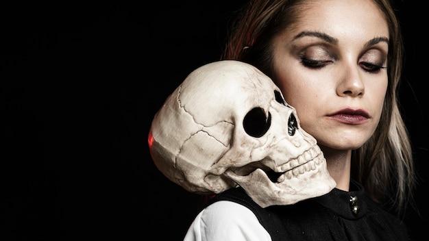 Vista lateral de mujer con calavera y espacio de copia