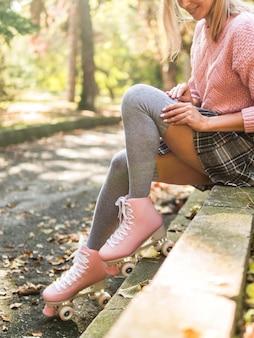 Vista lateral de la mujer en calcetines y patines sonriendo