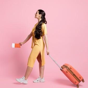 Vista lateral mujer caminando mientras sostiene su equipaje