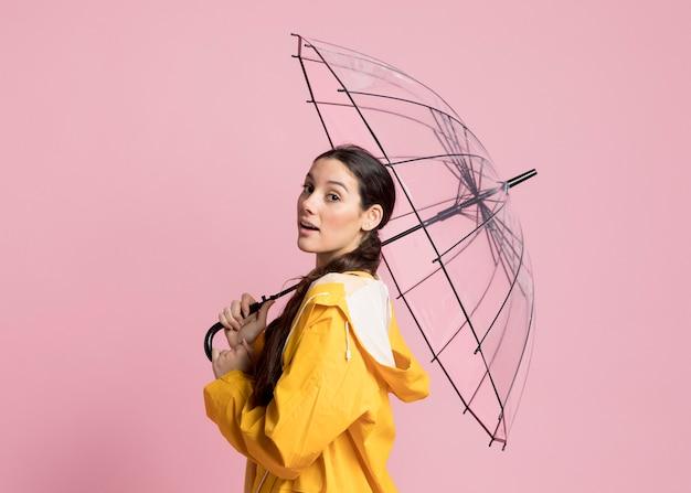 Vista lateral mujer caminando con un paraguas abierto
