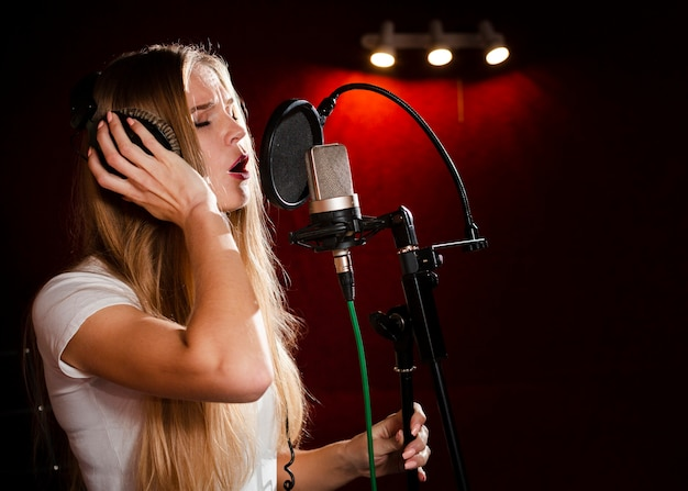 Vista lateral mujer cantando en el micrófono y con auriculares