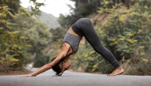 Vista lateral de la mujer en la carretera haciendo yoga
