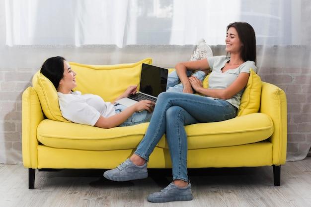 Vista lateral de la mujer en casa en el sofá con el portátil