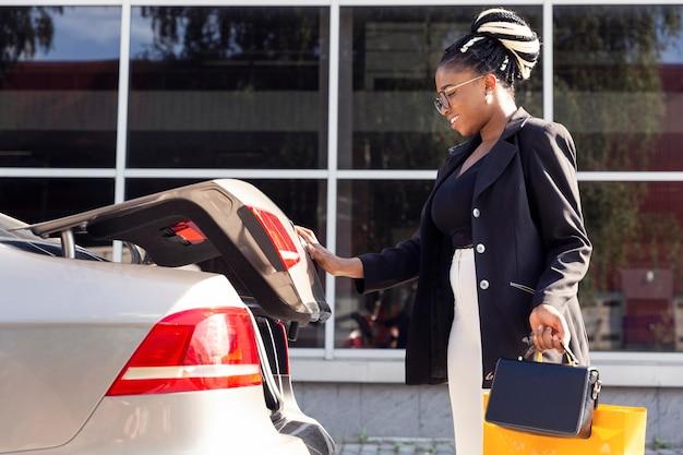 Vista lateral de la mujer cerrando el maletero de su coche
