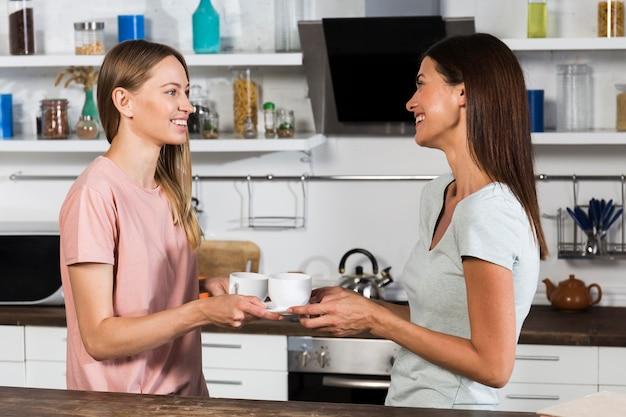 Vista lateral de la mujer charlando mientras toma un café en casa