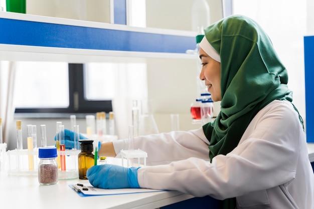 Vista lateral de la mujer científica con hijab y guantes quirúrgicos.
