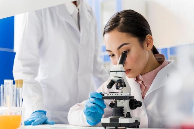 Vista lateral de la mujer científica en el laboratorio con microscopio