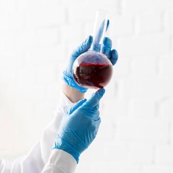 Vista lateral de la mujer científico sosteniendo cristalería de laboratorio con sustancia