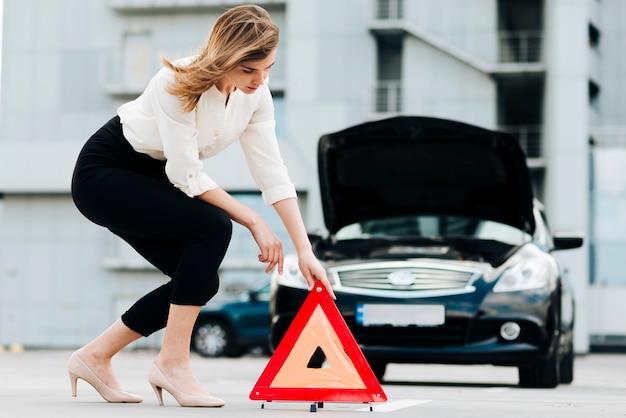 Vista lateral de la mujer colocando señal de emergencia