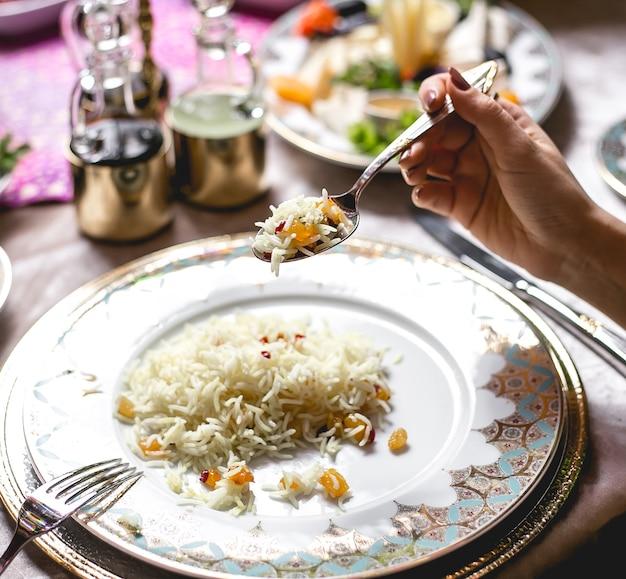 Vista lateral mujer come arroz hervido con pasas