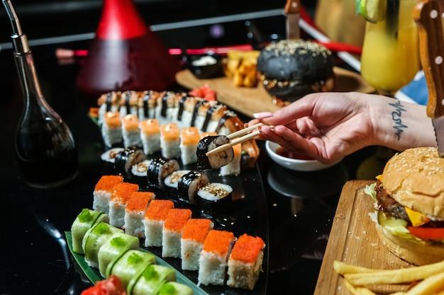 Vista lateral mujer come mezcla de rollos de sushi con salsa de soja y hamburguesas en la mesa