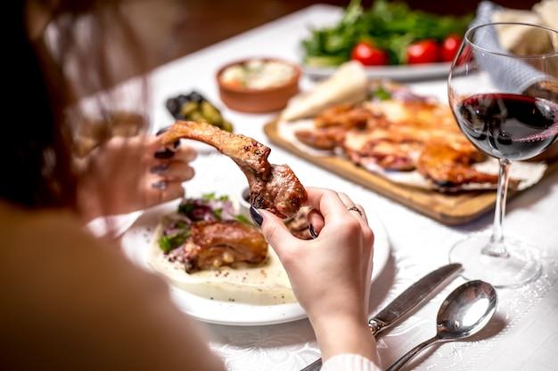 Vista lateral mujer comiendo costillas de cordero kebab con una copa de vino tinto