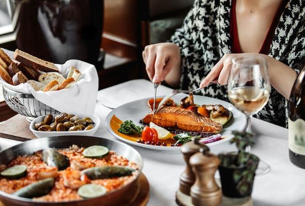 Vista lateral de una mujer comiendo salmón al horno con verduras en la mesa
