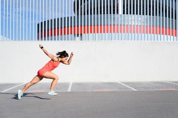 Vista lateral de una mujer corriendo