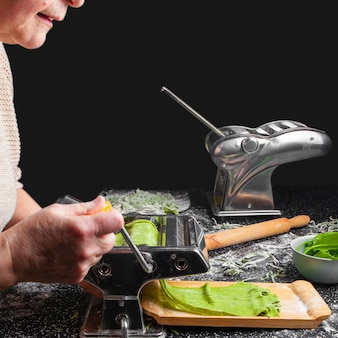 Vista lateral mujer corte pasta en cocina con utensilios de cocina sobre fondo negro.